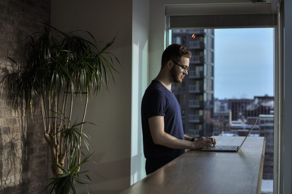 Man standing at his kitchen counter, working on laptop